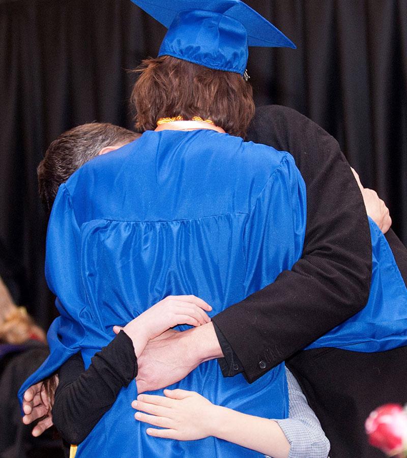 photo - parents surround and hug their graduating daughter
