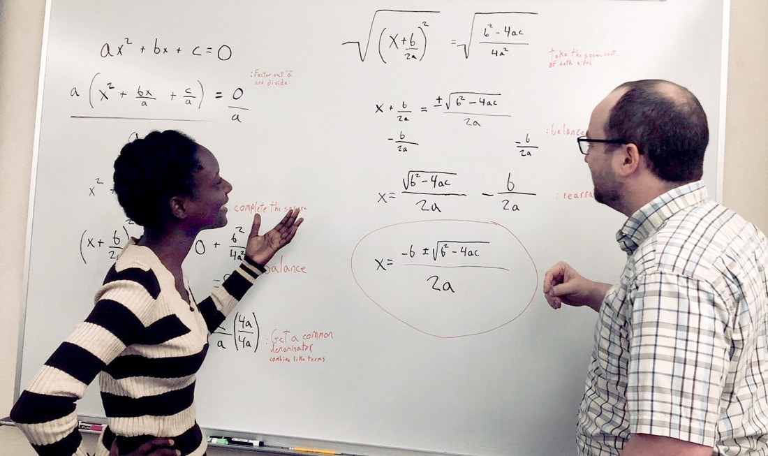 Student going over quadratic equation at a whiteboard with tutor